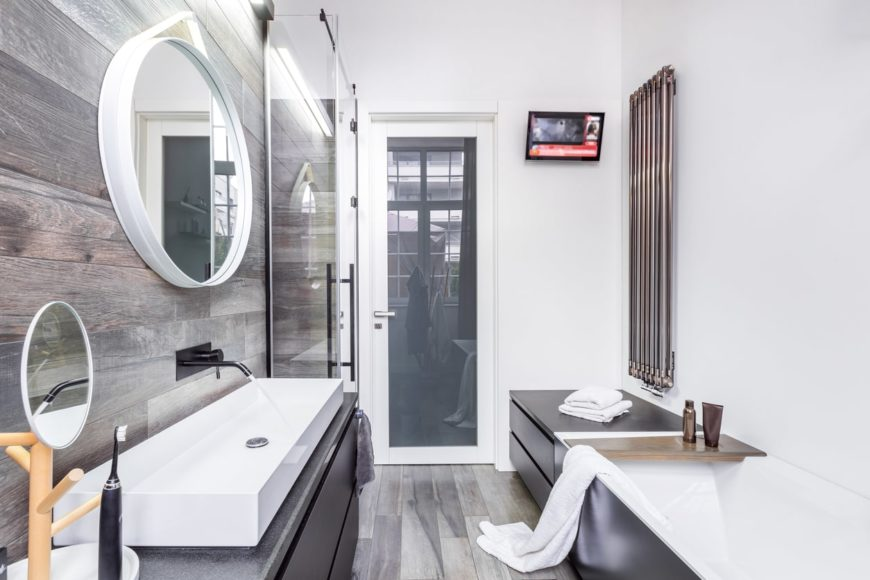 The rectangular bathtub is embedded into a black structure with black drawers topped with a stainless steel heater that stands out against the white walls matching the large rectangular sink basin against a wooden backsplash.