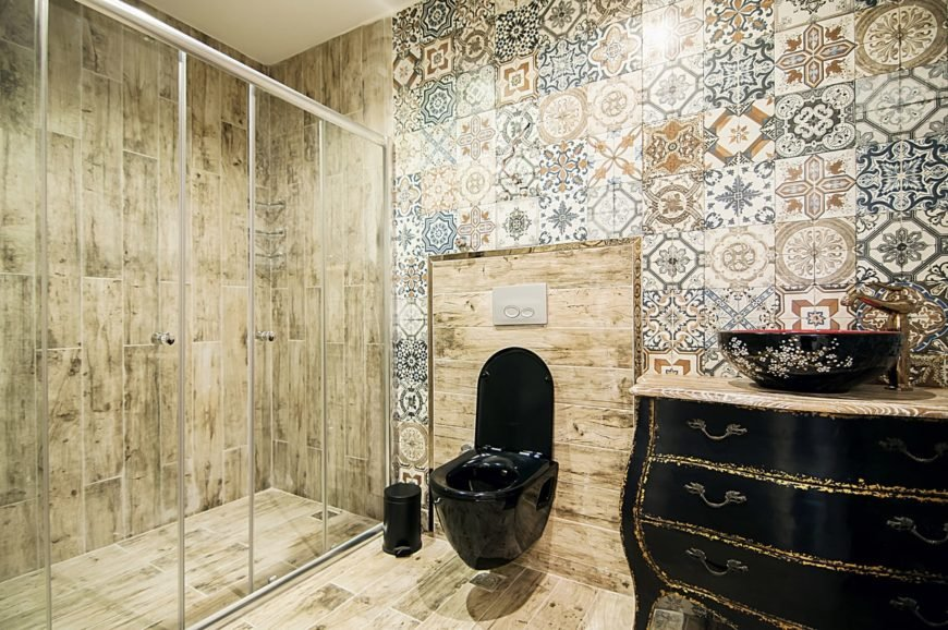 The elegant black floating toilet matches with the black curved vanity that has a black bowl sink over its wooden countertop. This stands out against the various patterned tiles of the wall.