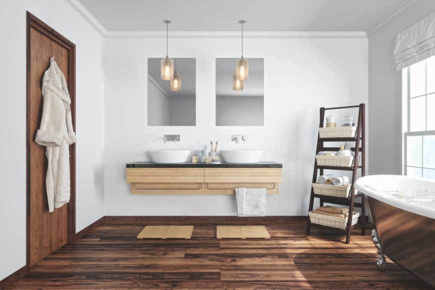 The brown facade of the freestanding bathtub matches well with the dark hardwood flooring complemented by the wooden floating vanity supporting two freestanding sinks topped with a couple of pendant lights and mirrors.