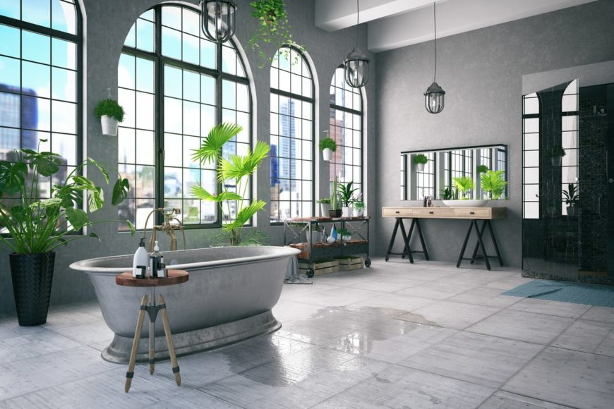 This spacious bathroom has a concrete-like gray flooring that complements the steel-gray freestanding bathtub matching with the textured gray walls dominated by tall arched windows that pairs well with the industrial-style pendant lights.