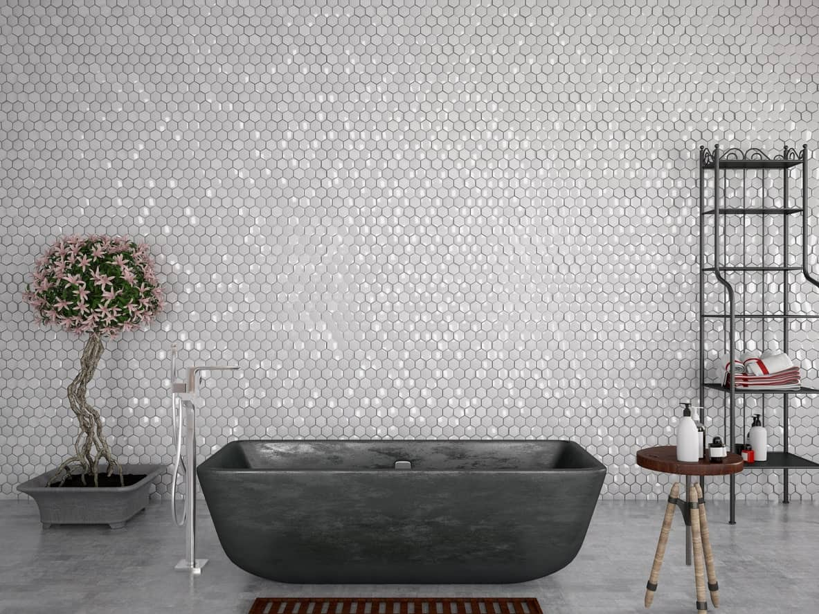 The wall of this bathroom is dominated by the small hexagonal floor tiles giving a nice textured wall background for the matte black freestanding bathtub with a potted plant on one side and a rod shelving on the other.