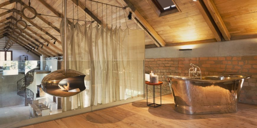 This loft-type bathroom has a hardwood flooring that goes perfectly well with the red brick walls that is contrasted by the metallic freestanding bathtub. This matches with the modern fireplace hanging from the wooden cathedral ceiling.