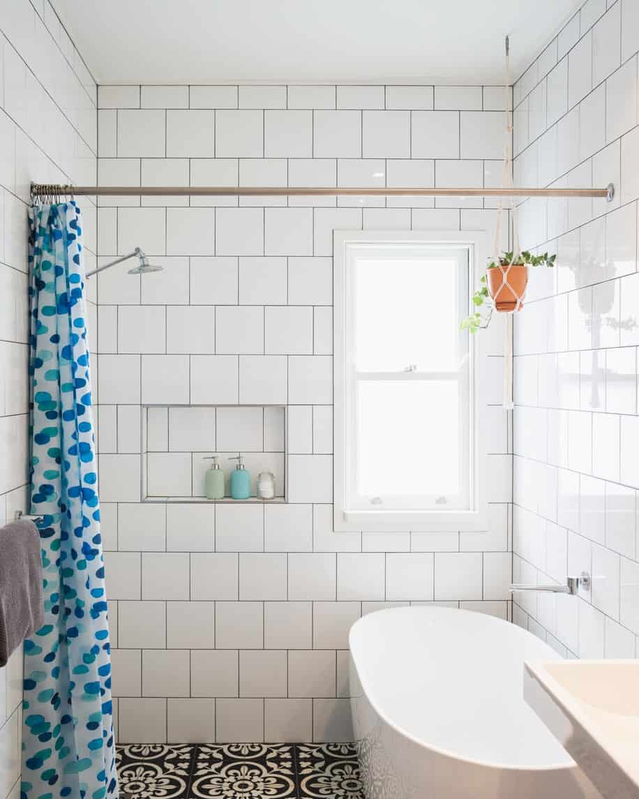 The white tiles of this simple bathroom is given a black grout to emphasize the brick wall pattern of the white tiles. This is a nice background for the white bathtub inside the shower area that has a patterned green shower curtain hanging on a brass rod.
