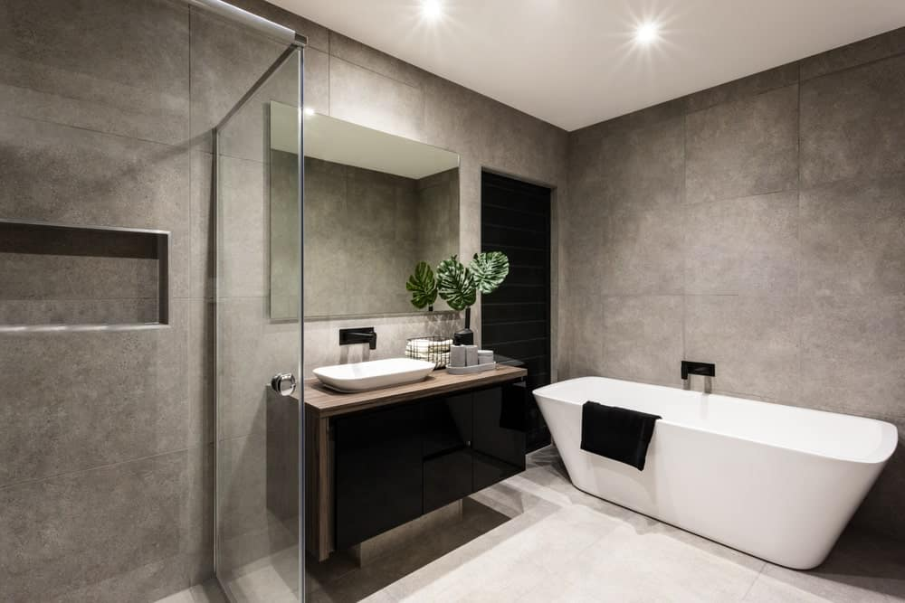 The walls of this simple bathroom has a gray concrete-like finish that sets an industrial-style tome to the white modern freestanding bathtub paired with a black faucet the same as the sink of the dark vanity.