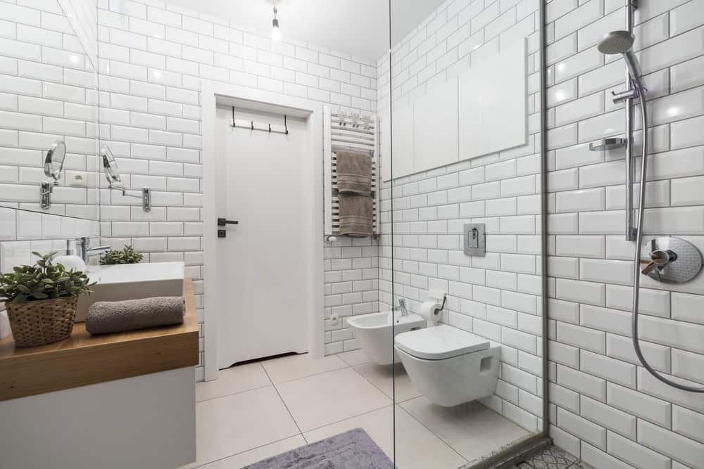 The white brick-like tiles of this simple bathroom are arranged in a brick wall pattern with black grout to emphasize the lines. This serves as a background for the white floating toilet and white vanity with a butcher block countertop.