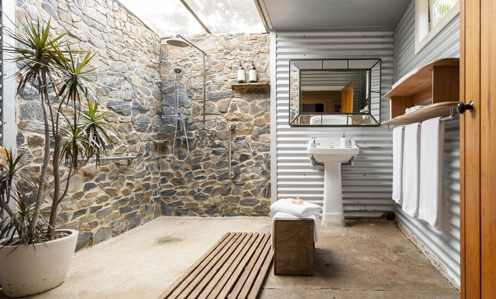 This is a charming bathroom divided in two sections. one section is the shower area with stone walls and a skylight. The other section is the area of the white pedestal sink that pairs with the tin roof material on the walls for that industrial-style look.