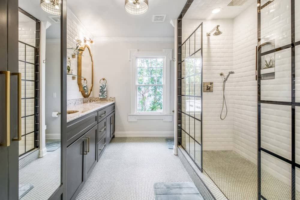 The grainy industrial-style flooring of this bathroom is paired well with the white tiles on the walls arranged in a brick wall pattern. This matched with black-framed glass walls for the shower area that has industrial-style fixtures.
