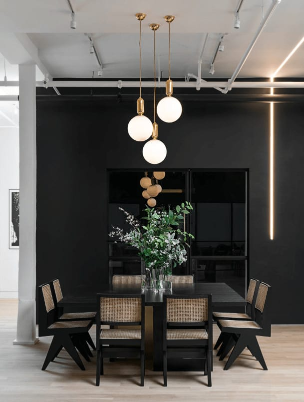 Black dining room features glass globe pendants and track lights mounted on the white ceiling lined with exposed pipes. It has a wooden dining table surrounded by woven chairs over light wood plank flooring.