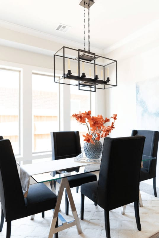 The gorgeous dining room boasts an industrial chandelier and black wingback chairs surrounding a glass top dining table lined with a white runner.