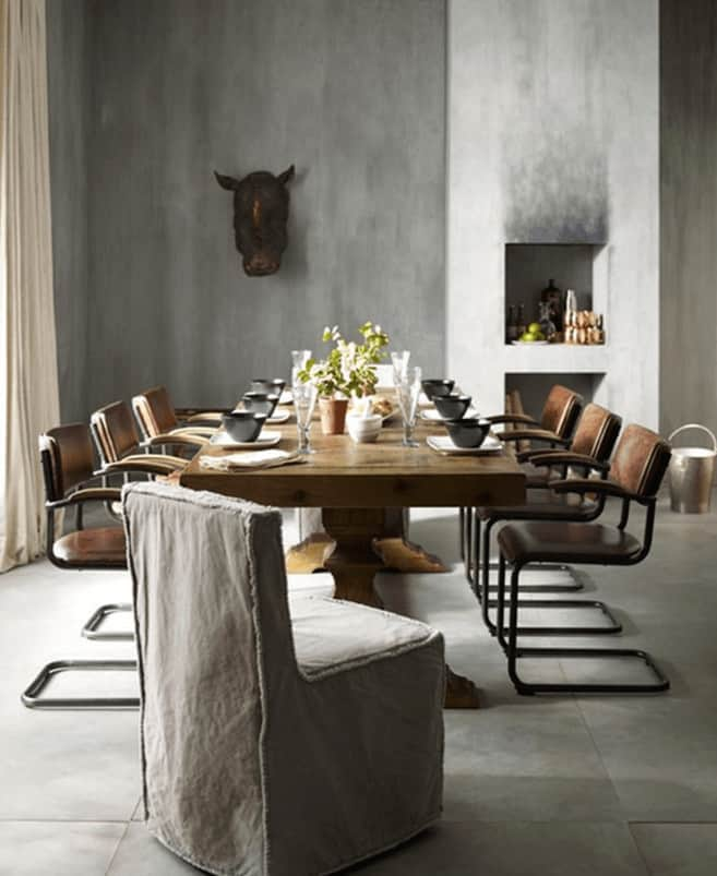 This dining room showcases a wooden dining table paired with brown leather and gray skirted chairs. It includes inset shelves and a faux animal head decor mounted on the concrete wall.