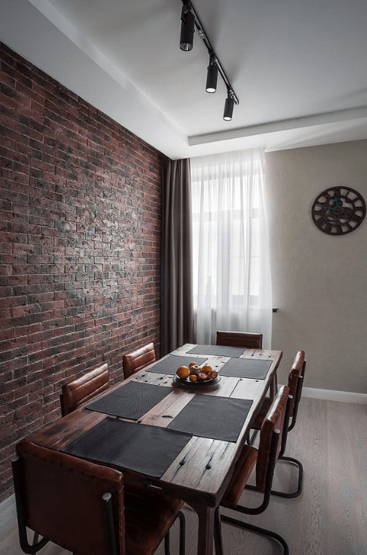 Simple dining room with rustic dining table and leather chairs placed against the red brick accent wall. It has light wood plank flooring and glazed windows covered with beige and white sheer curtains.