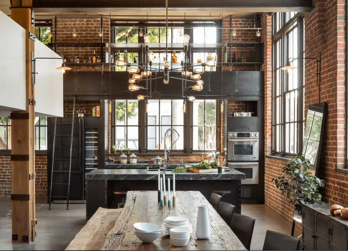 Industrial dining room with red brick walls and aluminum framed windows complementing with the bulb pendant that hung over the rustic dining table paired with a matching bench and black chairs.