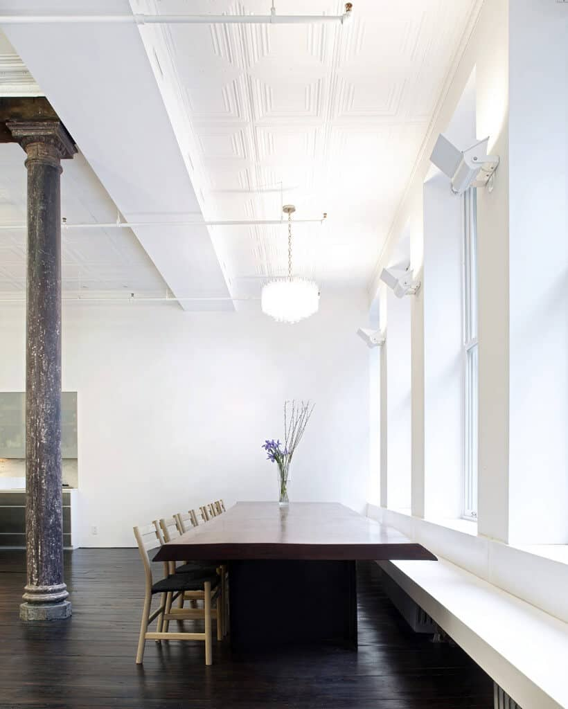 Industrial dining room with high ornate ceiling and dark wood plank flooring lined with a distressed column. It has a wooden dining table flanked by black cushioned chairs and a built-in bench by the glazed windows.