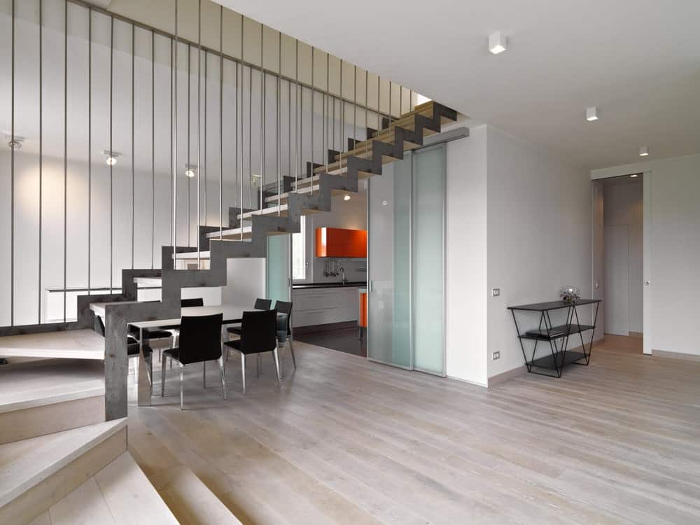 A dining space situated underneath the metal staircase fitted with light wood treads showcases a stylish table and black modern chairs over wood plank flooring.