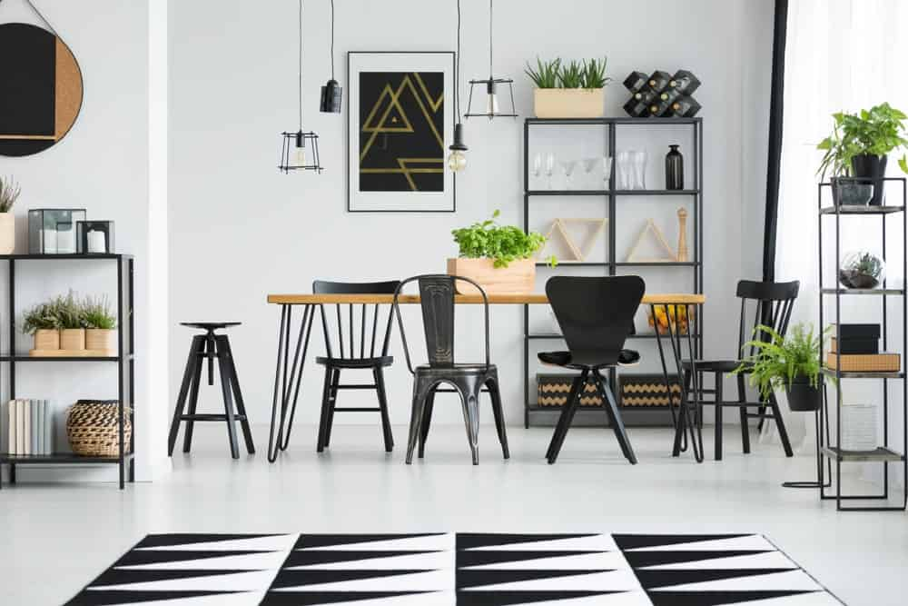 Industrial dining room decorated with geometric wall art and a striking area rug that lays on the smooth white floor. It has bulb pendants, metal shelving units and a wooden dining table that's surrounded with black seats in different styles.