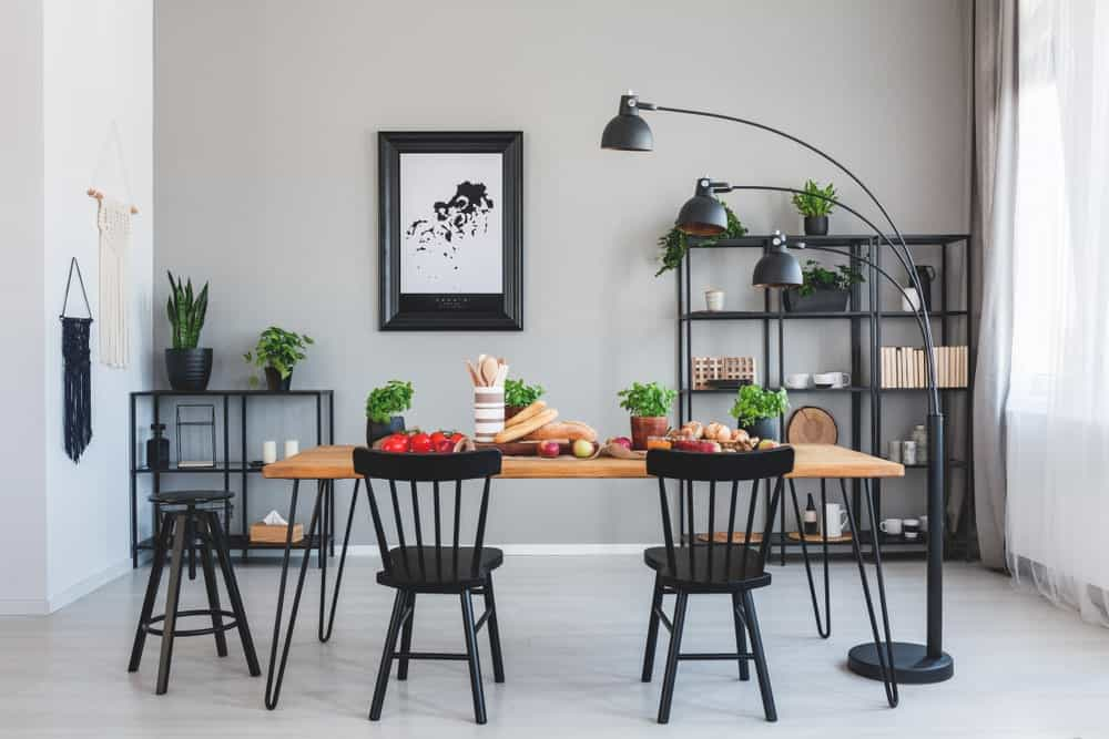 Fresh dining room with metal shelving units and black seats paired with a wooden table that's lighted by a three head floor lamp.