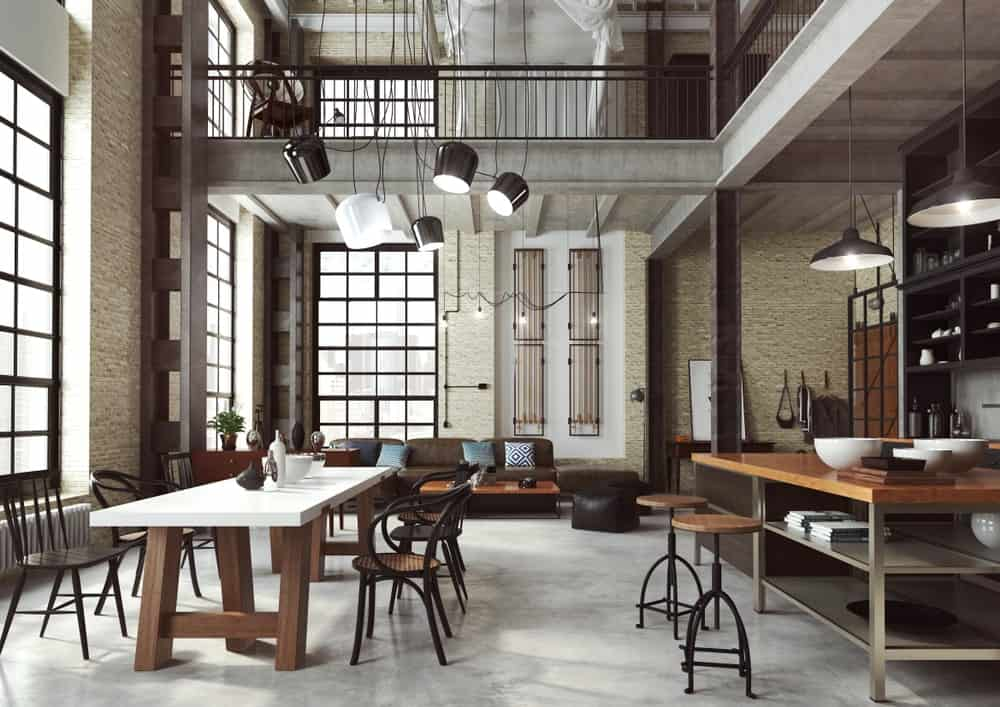 A dining space across the kitchen lighted by industrial pendants that hung from the high ceiling. It has a white dining table paired with metal round back chairs that sit on concrete flooring.
