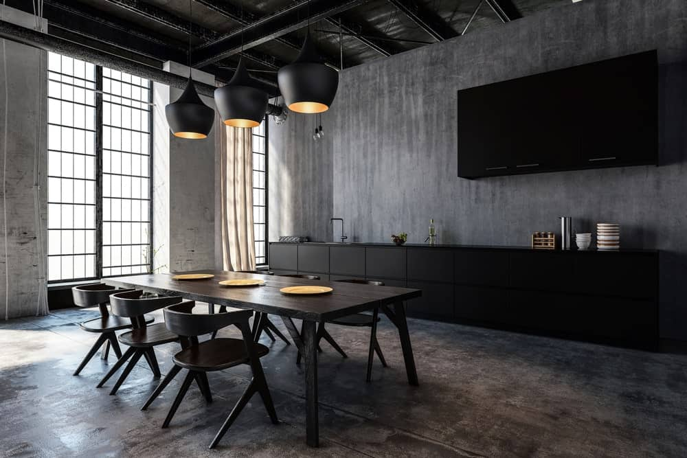 A dark dining room offers a wooden dining set on a distressed flooring and black pendant lights that hung from the beamed ceiling.