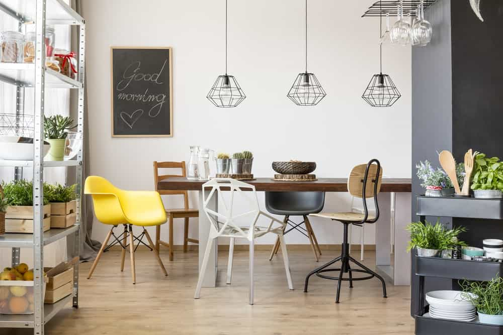 Industrial dining room illuminated by geometric pendants that hung over the wooden dining table surrounded with various styled chairs.