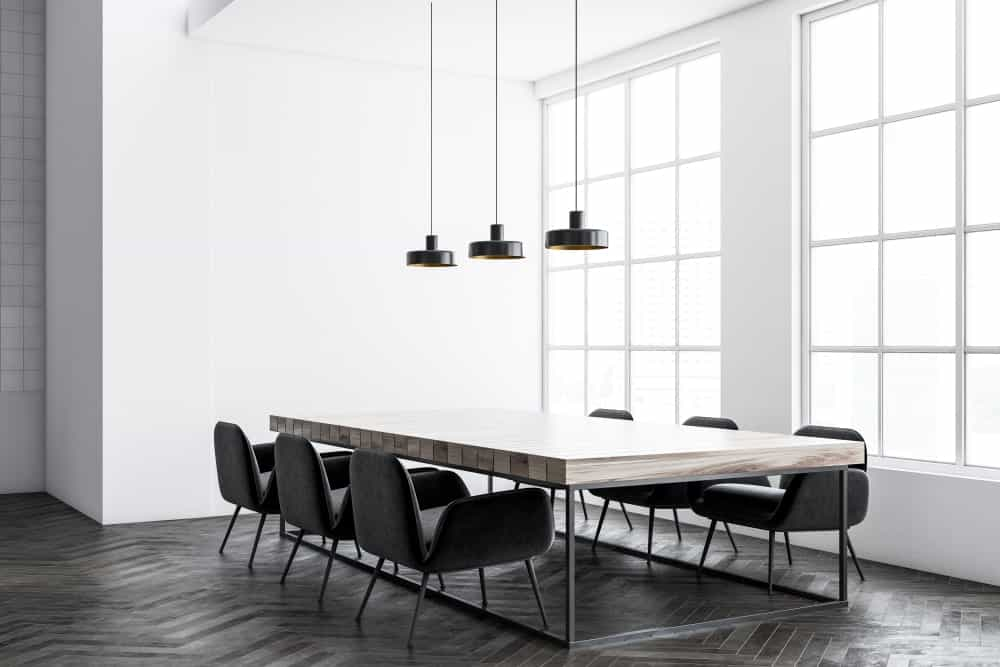 Natural light streams in through the white framed windows in this industrial dining room that sports a minimalist design. It has black dome pendants along with a rustic dining table and stylish black chairs that sit on dark wood flooring arranged in herringbone pattern.