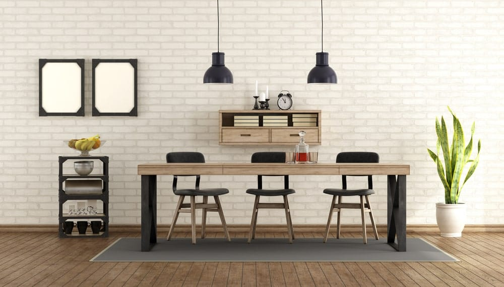 Fresh dining room with natural wood plank flooring and white brick wall mounted with black frames and floating shelf. It has a wooden dining set flanked by a small shelving unit and potted snake plant.