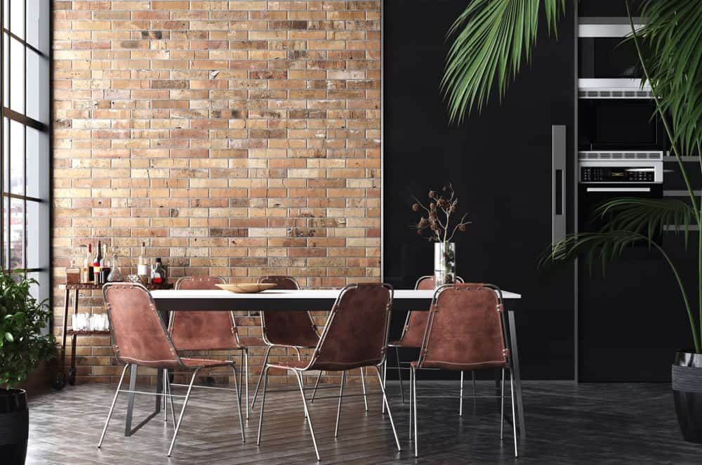 Brown dining chairs sit at a metal table in this industrial dining room with herringbone wood flooring and brick accent wall that adds character in the area.