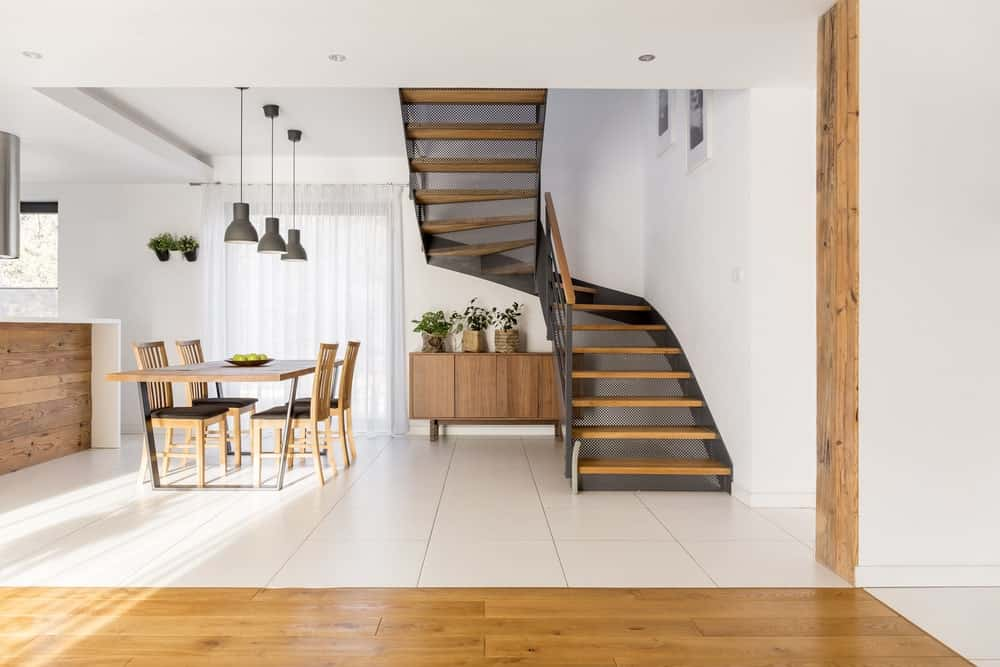 A dining area across the perforated staircase showcasing wooden dining set lighted by gray pendants and a buffet table topped with potted plants which bring a refreshing ambiance to the room.