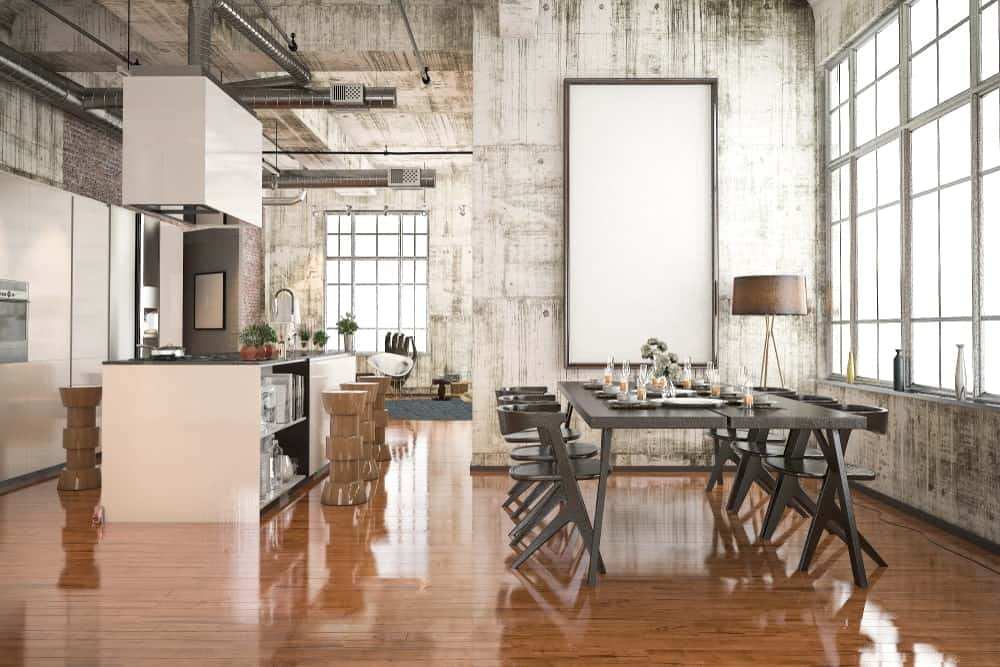 Industrial dining area with a hint of rustic design from the distressed white walls mounted with a blank frame. It has a drum floor lamp and gray dining set that sits on rich hardwood flooring.