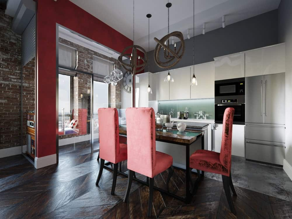 Distressed red high back chairs add a nice accent to this dining space boasting chevron wood flooring and industrial pendant lights that hung over the wooden dining table.