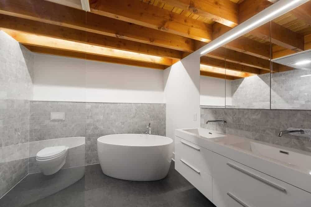 This industrial-style bathroom has a wooden ceiling with exposed wooden beams that contrast the white walls. These walls are dominated by the gray backsplash tiles that complement the white toilet, freestanding bathtub and the floating modern two-sink vanity.
