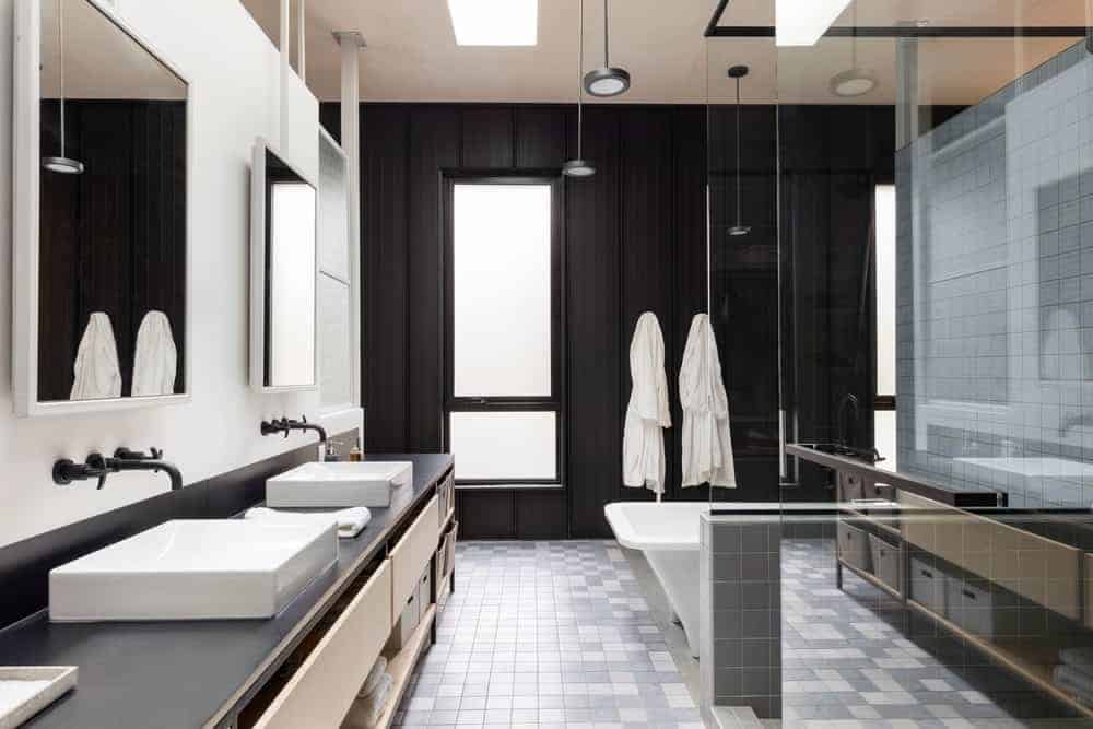 This bathroom has an industrial-style metal black wall on the far side that houses a window of frosted glass bringing in natural lights to the gray flooring tiles that complements the white bathtub and black countertop of the two-sink vanity.