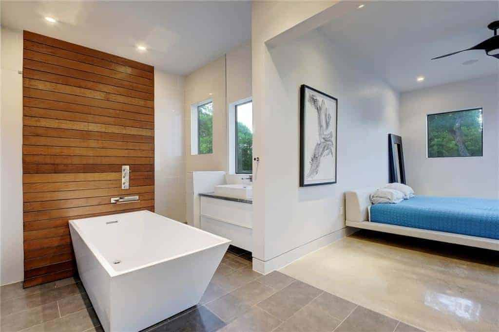 The rectangular freestanding white bathtub that stands out against the gray industrial-style flooring and its wall panel made of wooden planks embedded into the white wall. This setup is illuminated by the window above the modern white vanity.