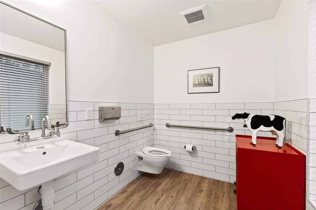 This simple bathroom has a hardwood flooring that complements the white wall tiles arranged in a brick wall patter that houses the floating porcelain toilet and sink with exposed pipes underneath. This makes the red drawer stand out adorned with a cow figurine.