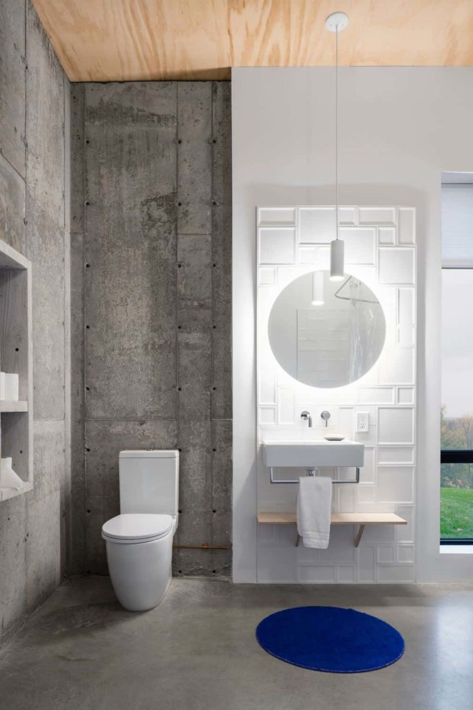 This simple bathroom has a bare wooden ceiling paired with gray concrete walls and flooring that contrasts the white modern toilet and the sink that is against a modern wall panel that is white, patterned and lit with white lights.