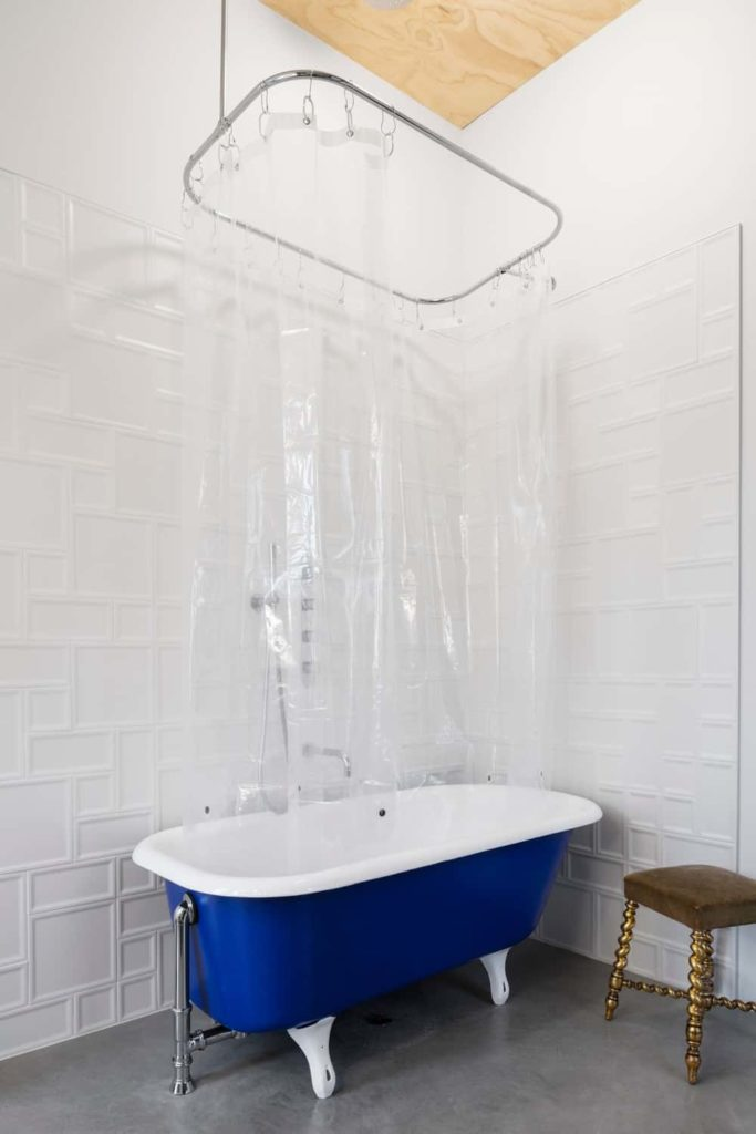 This bathroom has a blue and white freestanding bathtub in a corner of white patterned walls and gray concrete flooring. This bathtub also acts as a shower area with a see-through plastic shower curtain under a bare wooden ceiling.