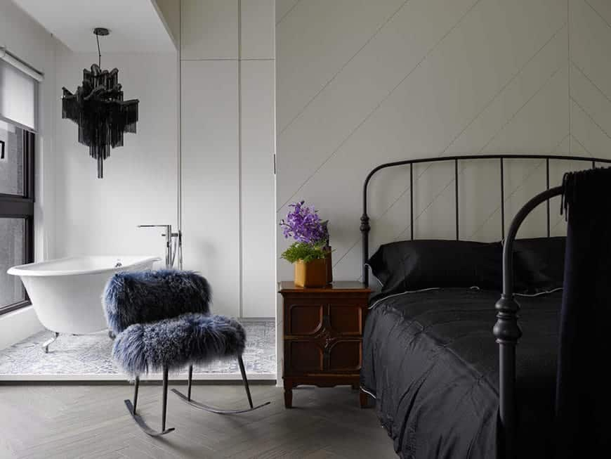 The gray hardwood flooring with a herring bone pattern of the bedroom leads to the open bathroom that has has a freestanding bathtub on complex patterned flooring tiles and topped with a peculiar black decorative lighting.
