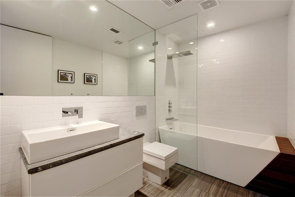 The porcelain white sink with its own built-in countertop matches with the white porcelain toilet beside it that stands out against the dark industrial-style tiles of the flooring that extends to the small glass-enclosed shower area.