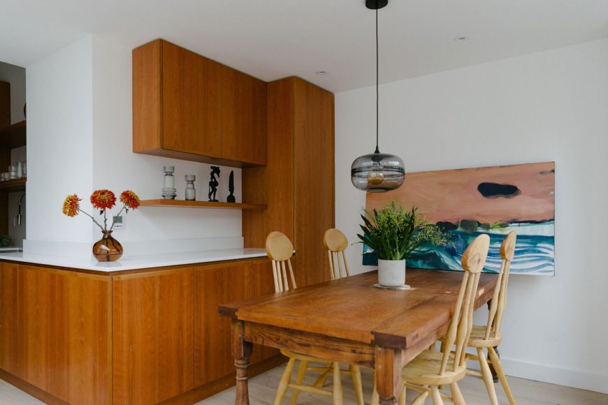 Cherry veneer kitchen with open shelving and a wood dining set.