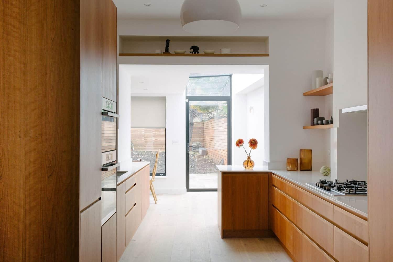 Cherry veneer galley kitchen with open shelving.
