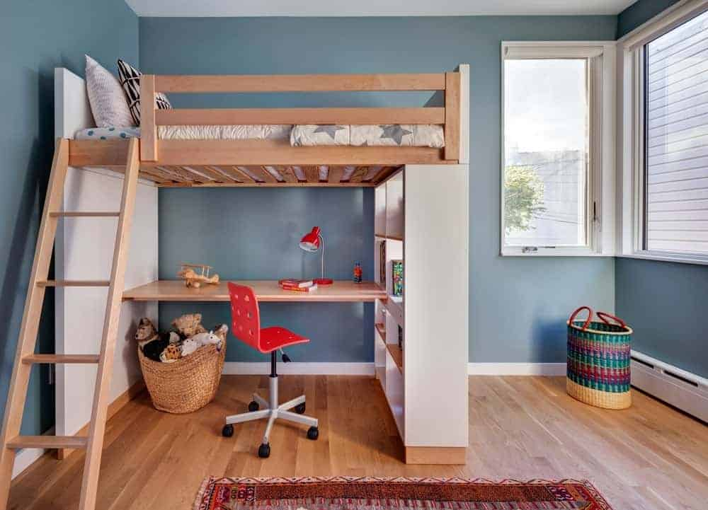 This bedroom features a loft bed with a desk underneath placed against the blue wall. It includes a red swivel chair and a brown area rug that lays on the wide plank flooring.