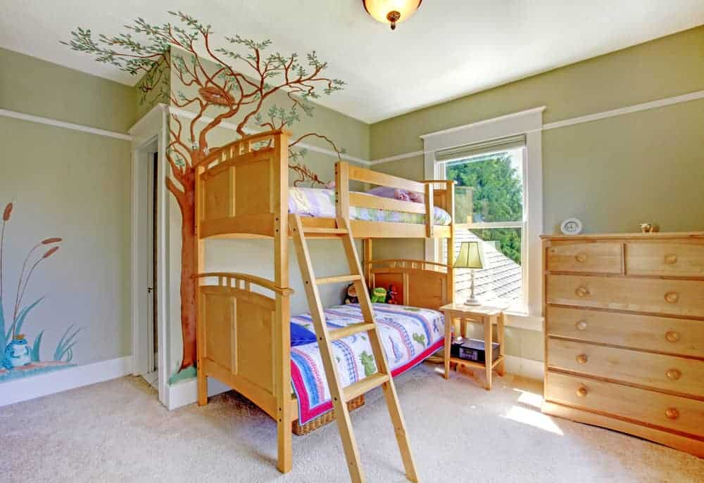 Kids bedroom furnished with a wooden bunk bed, drawer chest and a nightstand topped with a traditional table lamp. It has carpet flooring and taupe walls designed with plant and tree stickers.
