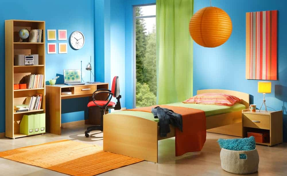 Kids bedroom that's bursting in bright colors showcasing a sleek bed and desk accompanied by a wooden nightstand and a shelving unit.