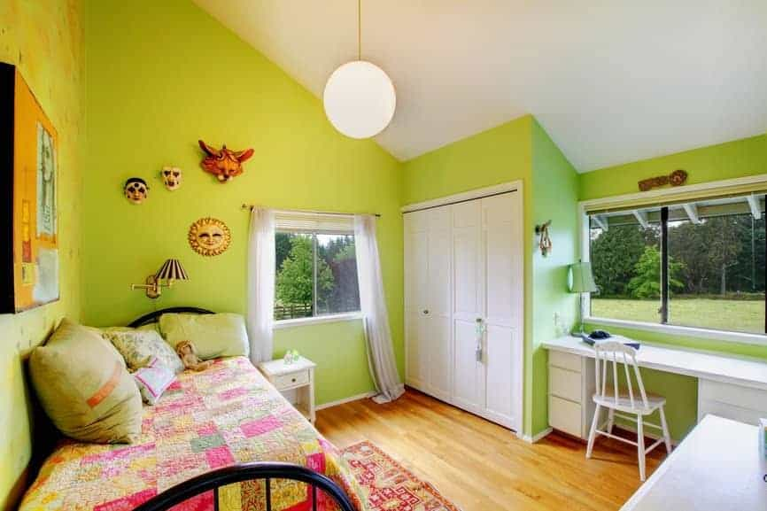 Green bedroom designed with head wall decors and a frosted glass globe pendant that hung from the vaulted ceiling. It has a black metal bed contrasted by a built-in wardrobe and white desk.