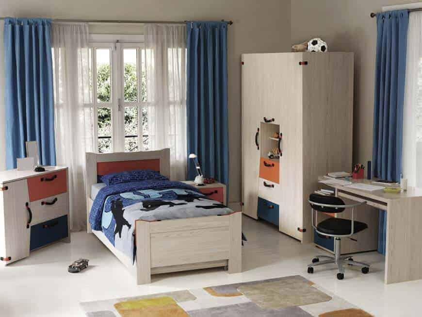 This bedroom showcases light wood furnishings that blend in with the walls and flooring for a cohesive look. It has subtle red and blue accents from the draperies, bedding and drawers.