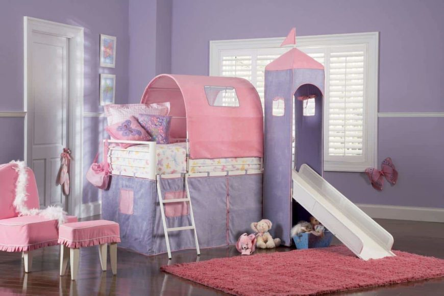 A charming girl's bedroom features a castle bed integrated with a white slide. It has pink and purple colors that blend in with the wall and furnishings.