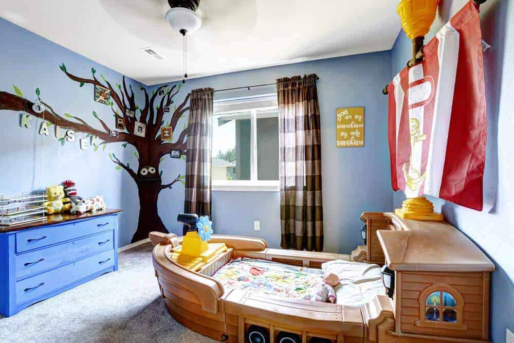 This boy's bedroom showcases a custom boat bed and a blue dresser placed against the light blue wall that's designed with a photo tree sticker. It has carpet flooring and glazed windows covered in brown striped drapes.