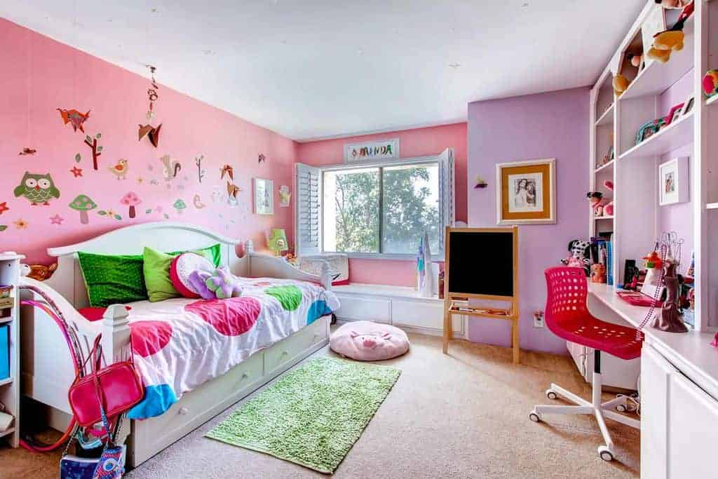 Gorgeous girl's bedroom offers a seat nook by the picture window, a white bed fitted with storage and a built-in desk with open shelving.