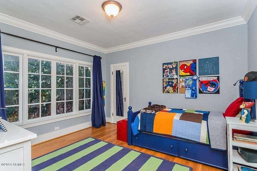 Blue bedroom decorated with marvel wall arts that are mounted across the bed wrapped in a colorful blanket. It has white framed windows and hardwood flooring topped by a striking striped rug.