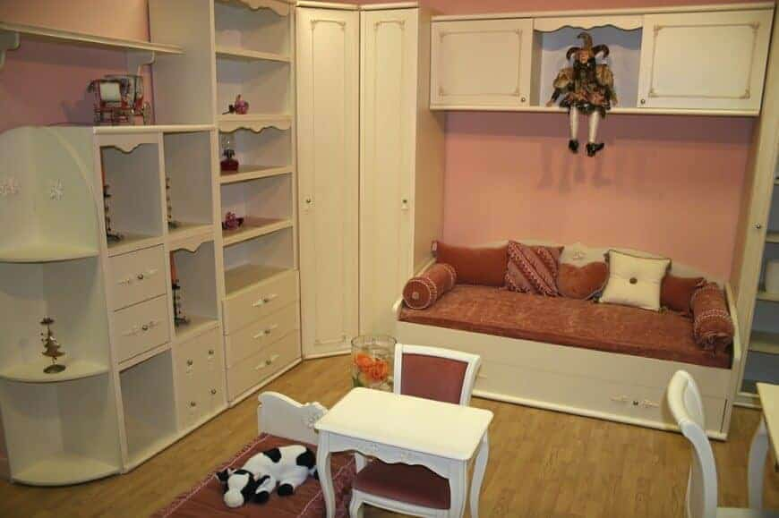 A clown doll sits on the floating cabinet in this kids bedroom with built-in storage and shelves along with a white bed that's topped with red mattress and pillows.