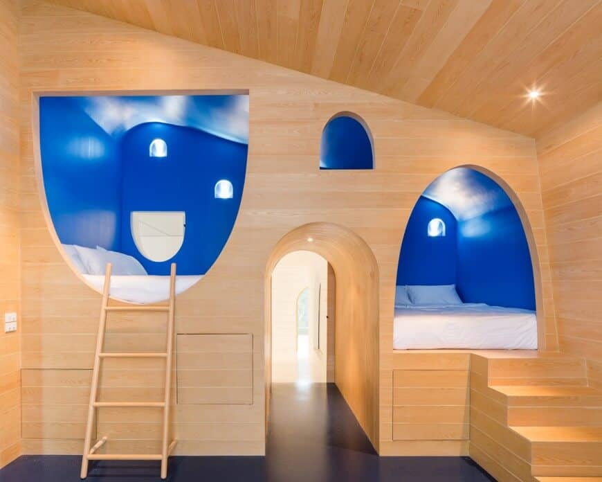 Kids bedroom with a creative design boasting blue alcove beds with an open archway in the middle. It has black flooring and smooth wood plank walls extending to the ceiling that's mounted with recessed lights.